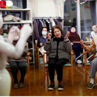 Les résidents suivent les mouvements effectués par le robot humanoïde 'Pepper' au cours d'un exercice d'après-midi au centre de soins Shin-tomi à Tokyo