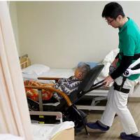 Un soignant habillé avec un ergosquelette pousse un fauteuil roulant à la maison de retraite Shin-tomi à Tokyo