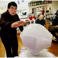 Un résident s'approche du robot humanoïde 'Pepper' pour se caresser la tête lors d'un exercice d'après-midi à la maison de retraite Shin-tomi à Tokyo.
